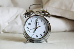 Alarm clock on bed sheets stock photo