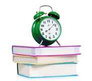 Alarm clock. Big green alarm clock with pile of books, isolated on white background Stock Photos