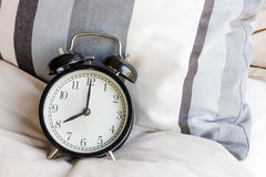 Alarm clock. Black alarm clock on cozy bed Stock Photo
