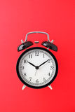 Alarm clock. Black alarm clock on red paper background Stock Image