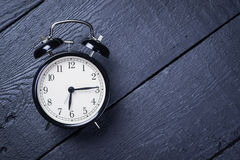 Alarm clock on a black wooden surface Stock Images