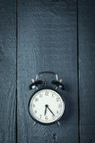 Alarm clock on a black wooden surface Royalty Free Stock Photo