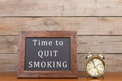 Alarm clock and blackboard with text & x22;Time to quit smoking& x22; royalty free stock images