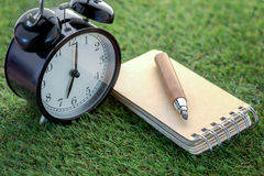 Alarm clock and blank paper with sharp pencil.jpg Royalty Free Stock Photo