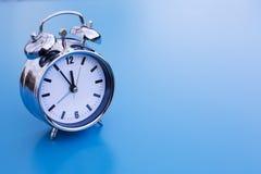 Alarm clock on blue table Stock Photo