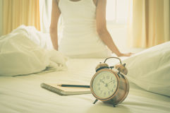 Alarm clock with book and girl on background. Vintage filtered Royalty Free Stock Photos