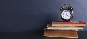 Alarm clock with books stock images