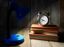 Alarm clock and books. On wooden background. Royalty Free Stock Images