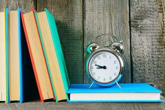 Alarm clock and books on a wooden shelf. Stock Photo