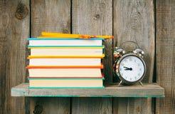 Alarm clock and books on wooden shelf. Stock Photos