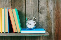 Alarm clock and books on wooden shelf. Stock Images