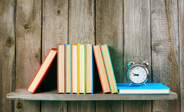 Alarm clock and books on wooden shelf. Stock Photo