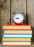 Alarm clock and books on wooden shelf. Royalty Free Stock Image