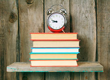 Alarm clock and books on wooden shelf. Royalty Free Stock Photos