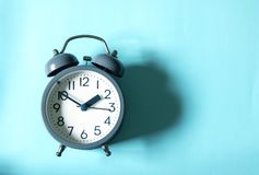 The Alarm clock on bright blue background , time management conc stock photo