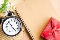 Alarm clock and brown diary. Royalty Free Stock Photos