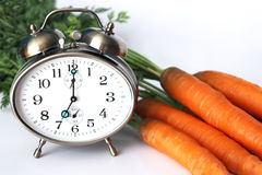 Alarm clock at bunch of carrots Stock Photo