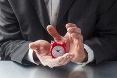 Alarm clock in businessman hands for time management Stock Images