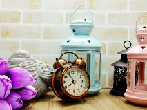 Alarm clock and candle light lantern with flowers bouquet home decor. Ation royalty free stock images