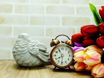 Alarm clock and candle light lantern with flowers bouquet home decor. Ation stock image