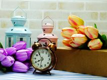 Alarm clock and candle light lantern with flowers bouquet home decor. Ation royalty free stock photography