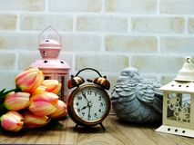Alarm clock and candle light lantern with flowers bouquet home decor. Ation stock photography