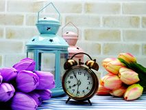 Alarm clock and candle light lantern with flowers bouquet home decor. Ation royalty free stock photo