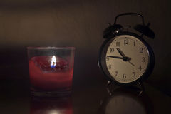 Alarm clock and candle Royalty Free Stock Photos