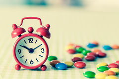 Alarm Clock and candy on the table instagram photo Royalty Free Stock Photography