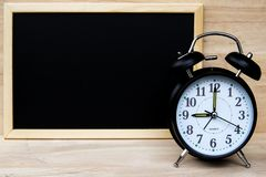 Alarm clock and chalkboard or blackboard for your text show board plan with time and Back to school concept. Alarm clock and chalkboard or blackboard for your stock images