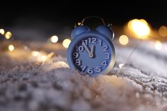Alarm clock and Christmas lights on white snow. Midnight countdown. Alarm clock and Christmas lights on white snow outdoors. Midnight countdown stock images