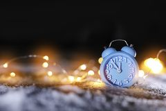 Alarm clock and Christmas lights on white snow outdoors, space for text. Midnight countdown stock photography