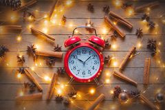 Alarm clock and cinnamon, star anise with Christmas lights Stock Images