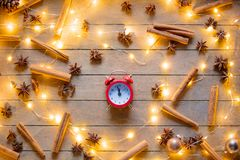 Alarm clock and cinnamon, star anise with Christmas lights. Vintage alarm clock and cinnamon, star anise with Christmas lights around on wooden background Royalty Free Stock Photography