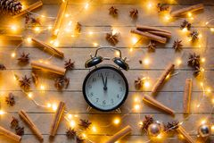 Alarm clock and cinnamon, star anise with Christmas lights. Vintage alarm clock and cinnamon, star anise with Christmas lights around on wooden background Stock Image