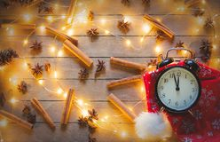 Alarm clock and cinnamon, star anise with Christmas lights. Vintage alarm clock and cinnamon, star anise with Christmas lights around on wooden background Royalty Free Stock Photo
