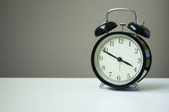 Alarm Clock. Classic alarm clock on white table and grey background Royalty Free Stock Photography