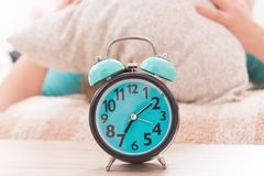 Alarm clock close to bed stock photography
