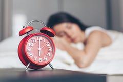 Alarm clock closeup and Young sleeping woman stock images