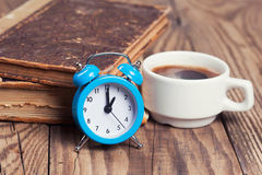 Alarm clock with coffe cup and vintage books Royalty Free Stock Image