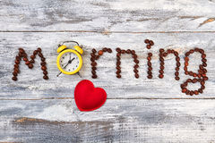 Alarm clock and coffee art. Red heart on wooden table Stock Image