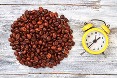 Alarm clock and coffee beans. Coffee grain on wooden background. Time to have a lunch Stock Image