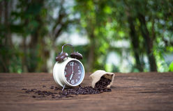 Alarm clock with coffee beans on wooden table Stock Images
