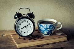 Alarm clock with coffee cup Stock Photos