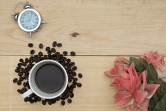 Alarm clock, coffee and flowers on wood table Stock Photography