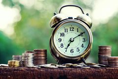 Alarm clock and coin stacks on wooden table with blur green garden background, bright morning color tone, finance and business. Concept, copy space stock image