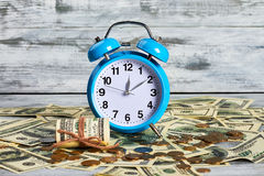 Alarm clock, coins and dollars. Time to earn money Stock Image