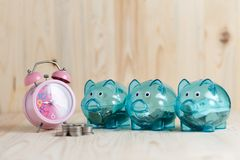 Alarm clock and coins put on the wood table. Clear piggy bank with 3 pigs, which has money in it. Placed on a wooden background. Saving money on time to Stock Photography