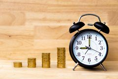 Alarm clock and coins stack on wood table and wooden background, savings money concept. Alarm clock and coins stack on wood table and wooden background show royalty free stock photo