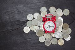 Alarm clock and coins on wooden table, Money savings, Investment, growing concept, Stacking growing coins, Saves money for the royalty free stock images